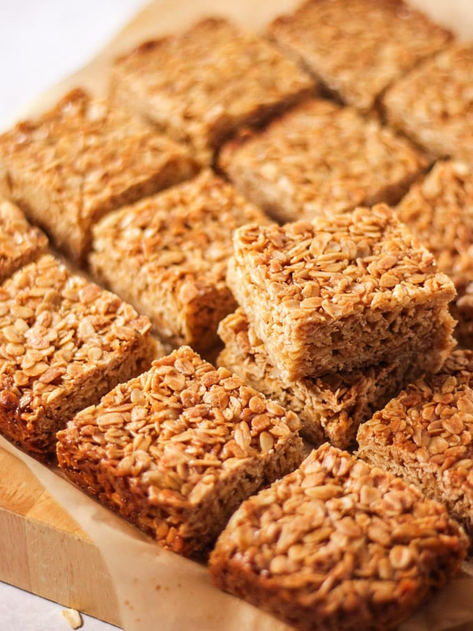 Pieces of square flapjack from a side angle on top of baking paper with one piled on top.