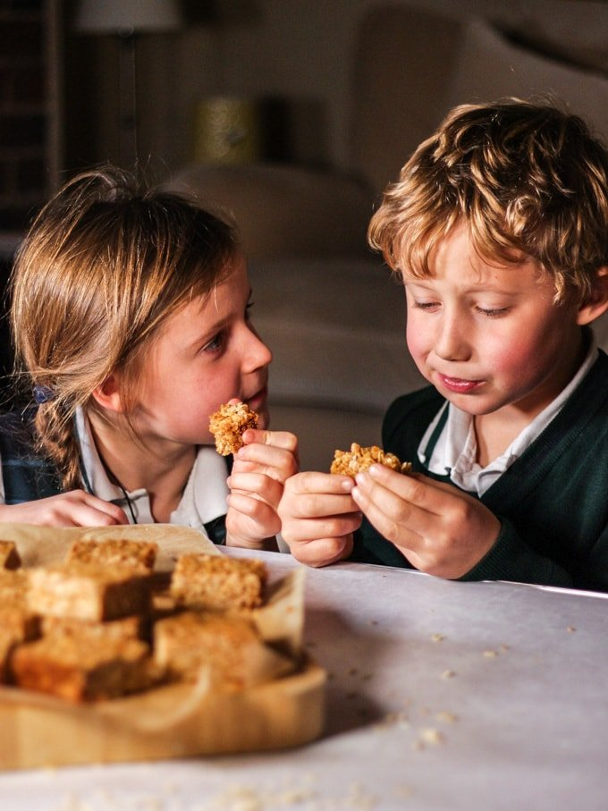 Two young children eating flapjacks.