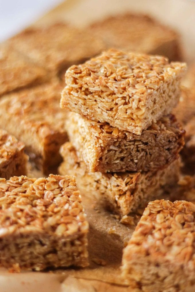 Pieces of square flapjack from a side angle on top of baking paper with two piled on top.