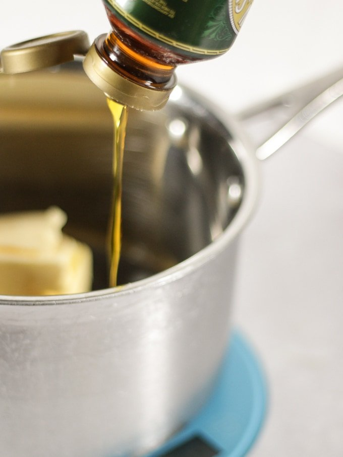 Golden syrup pouring into a metal saucepan on a blue weighing scale.