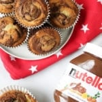 Overhead photo of a pile of Nutella muffins on a plate with a red cloth with white stars under it, one opened muffin and a jar of Nutella