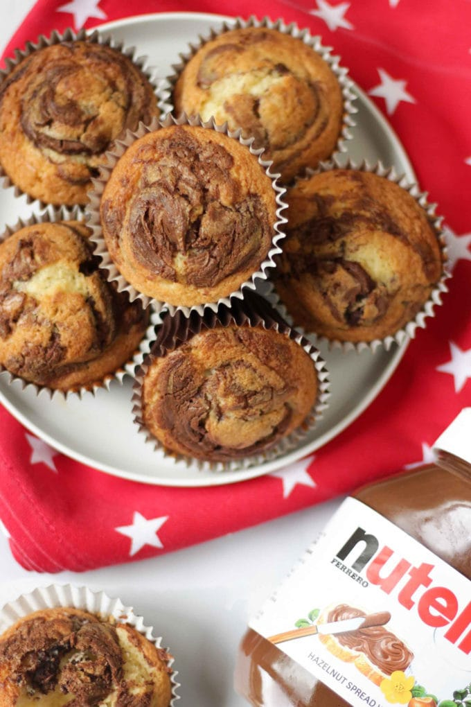 Overhead photo of Nutella Muffins on a white plate on a red tea towel with white stars on with white background.