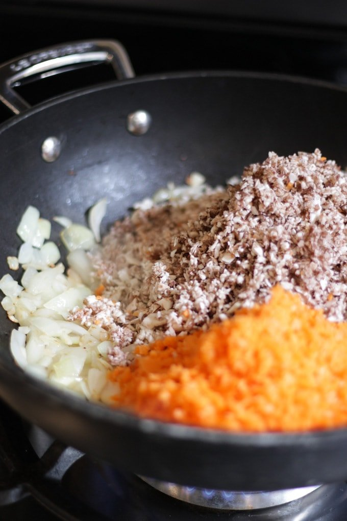 Very finely chopped mushrooms and carrots and onions in a le creuset wok frying pan for making pork yuk sung recipe.