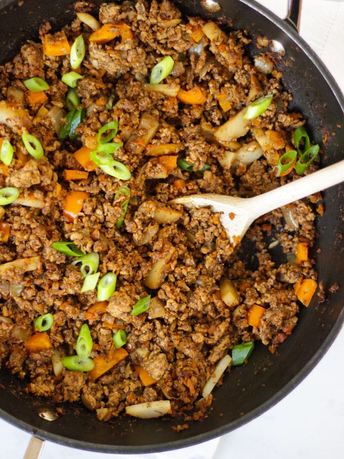 Overhead photo of a black le creuset wok filled with pork yuk sung made with pork mince sprinkled with spring onions with a wooden spoon in the wok.