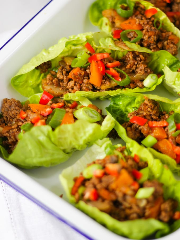 Yuk sung cooked pork mince in lettuce leaves side view in a white enamelware dish on white napkin and white marble background.