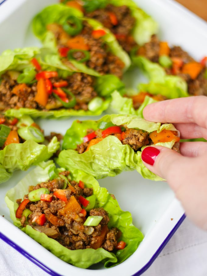 Hand with red painted finger nails picking up a lettuce cup of yuk sung from a white enamelware dish.
