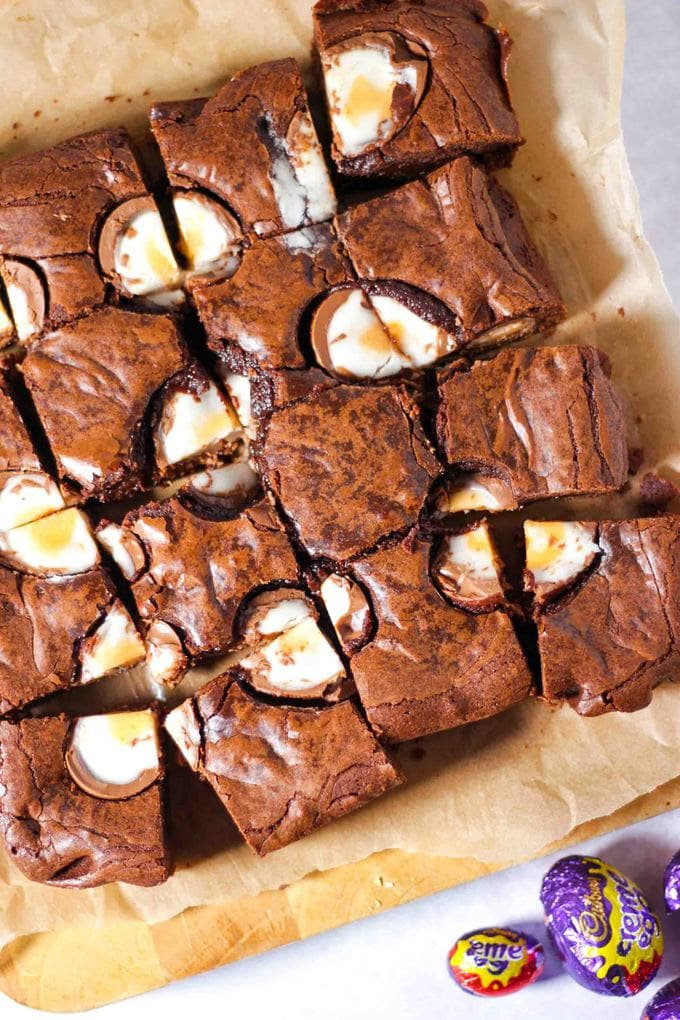 Creme Egg Brownie squares on baking paper on a white background with creme eggs in foil on the side