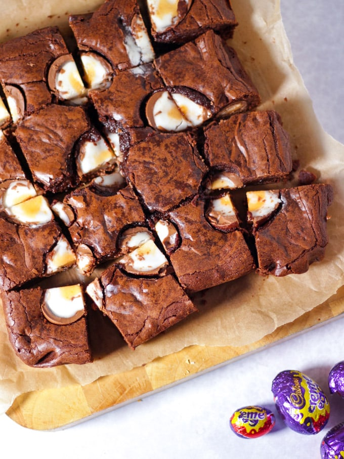 Creme Egg Brownies cut into squares topped with chocolate creme eggs cut in half