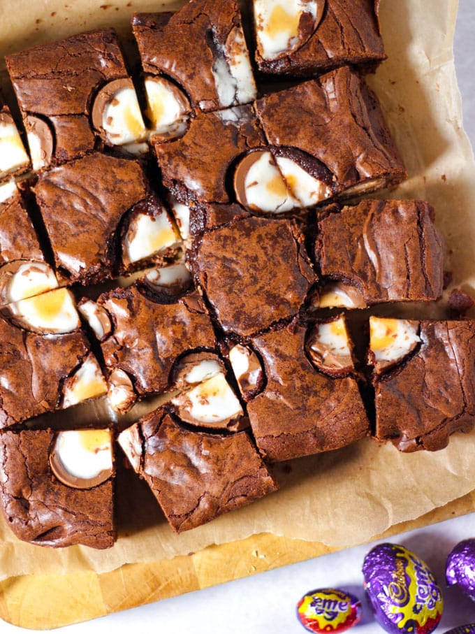 Creme Egg Brownies, cut into squares on a chopping board with foil wrapped creme eggs on the board and topped with cut chocolate creme eggs.