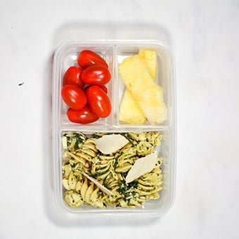 plastic lunchbox filled with pesto pasta, healthy lunch idea for work