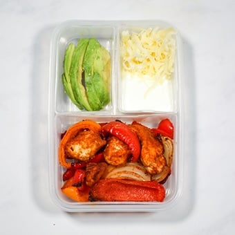 Leftover chicken fajitas in a plastic compartment lunchbox as a healthy lunch