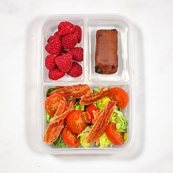 Lunchbox with BLT salad, raspberries and malt load