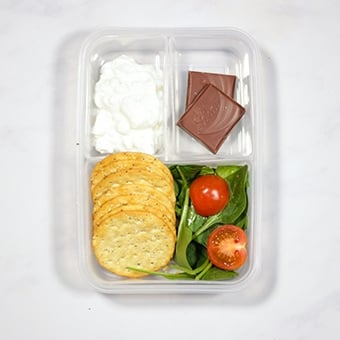 Healthy lunch box idea, cottage cheese, crackers and spinach
