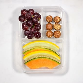 healthy lunchbox idea of fruit salad and protein balls