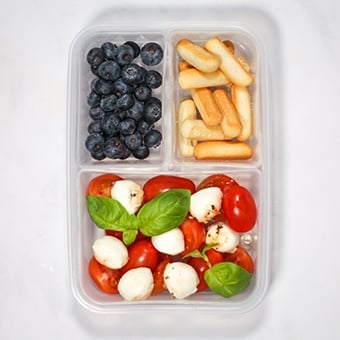 Plastic lunchbox with tomato mozzarella salad, healthy lunch idea for work