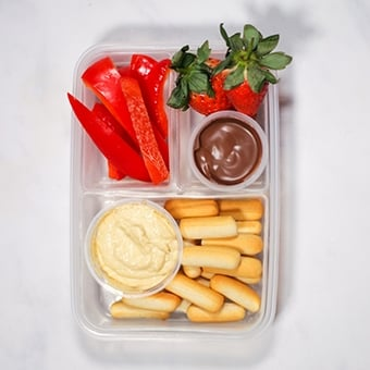 Plastic lunchbox with hummus, breadsticks, strawberries healthy lunch idea for work
