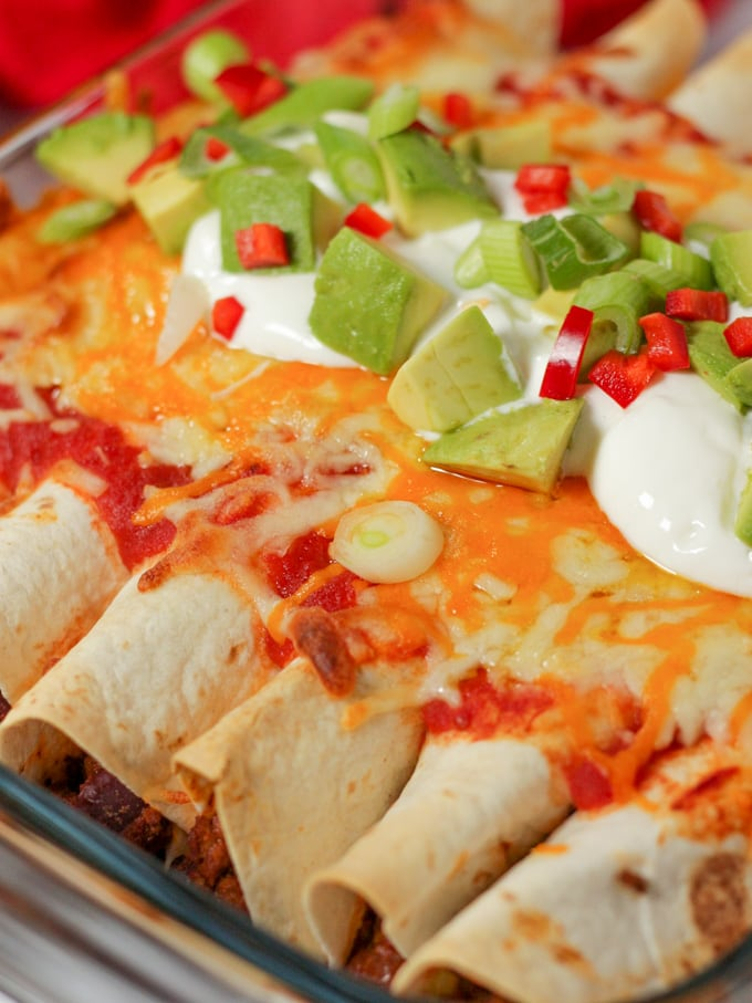 Cheese enchiladas topped with yoghurt and Mexican accompaniments