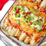 Beef enchiladas topped with cheese and avocado and chilli