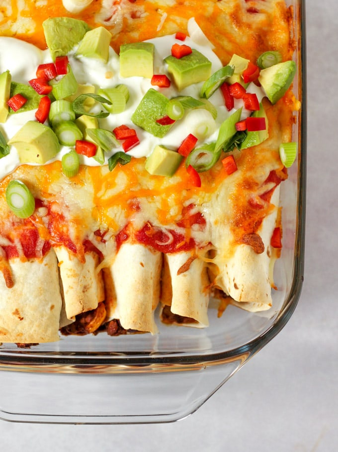 Casserole dish of beef enchiladas topped with sour cream and chilli and avocado.