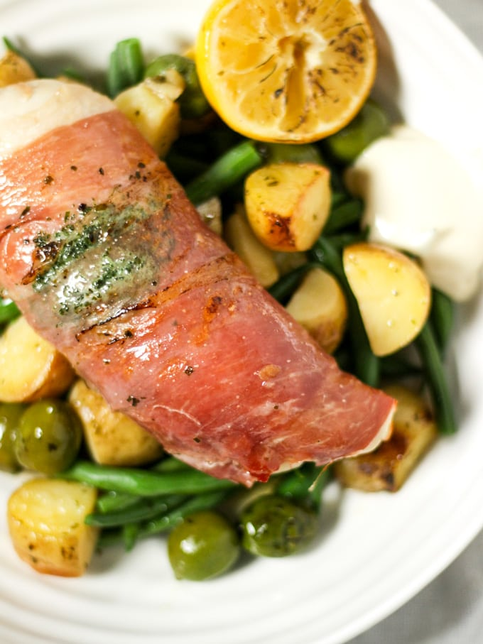 Chicken breast wrapped in bacon with green beans, potatoes, and olives