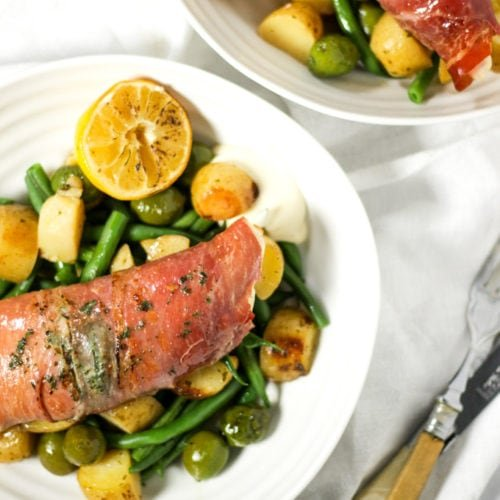 Chicken wrapped in bacon on white plates with green beans, olives and potatoes