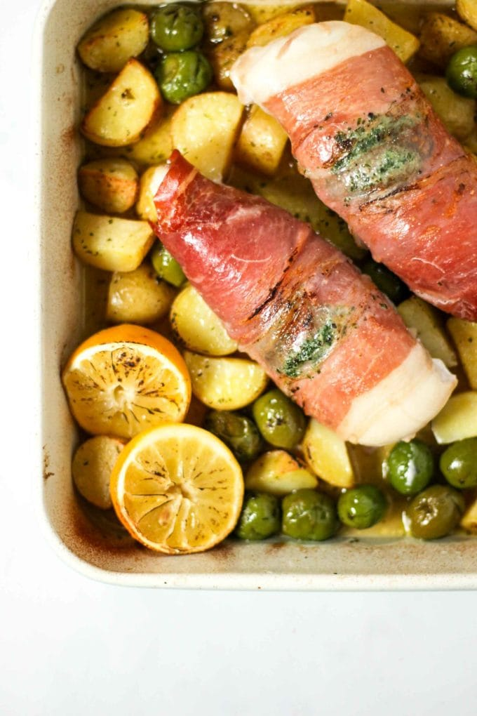 Chicken wrapped in bacon with potatoes, olives and lemon