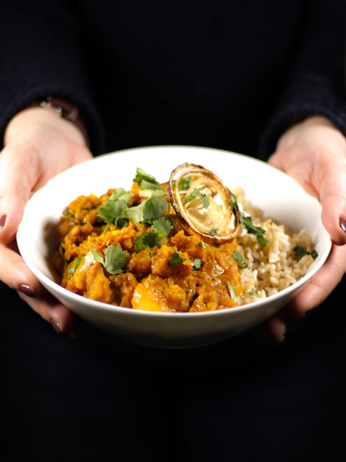 hands holding a bowl of red lentil Dahl with onions and coriander on top