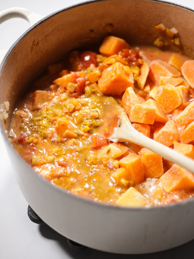 red lentil dhal with butternut squash added in a pan with wooden spoon