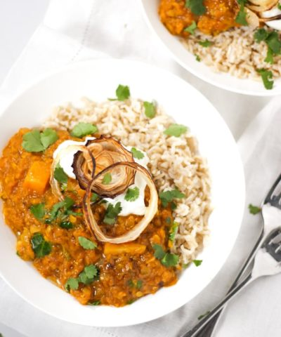 two bowls of red lentil Dahl and rice topped with onions in white bowls
