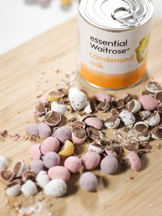Crushed mini eggs and can of Condensed Milk for making Mini Egg Fudge on a wooden chopping board.