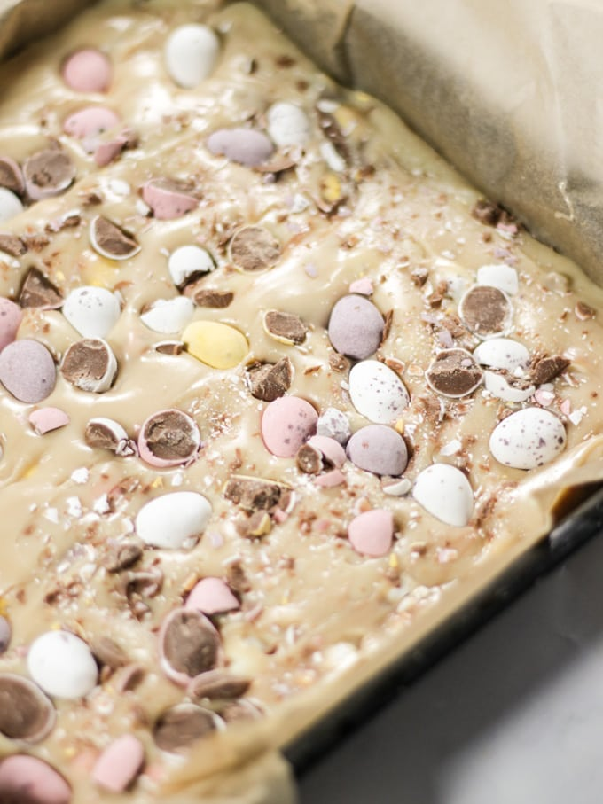 Mini Egg fudge mixture in a black metal tray before going into the fridge.