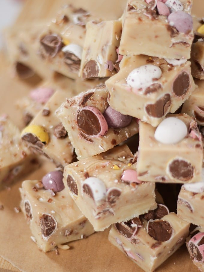 Pile of mini egg fudge cubes on a wooden board.