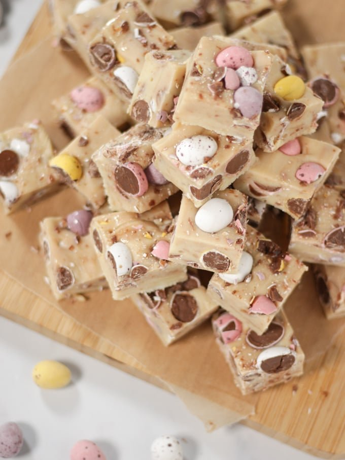 Pile of cubes of mini egg fudge on a wooden board.