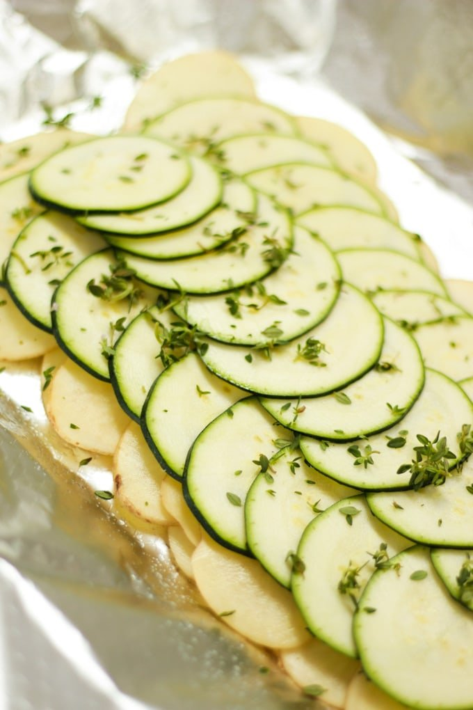 slices of raw potato and courgette layered on foil