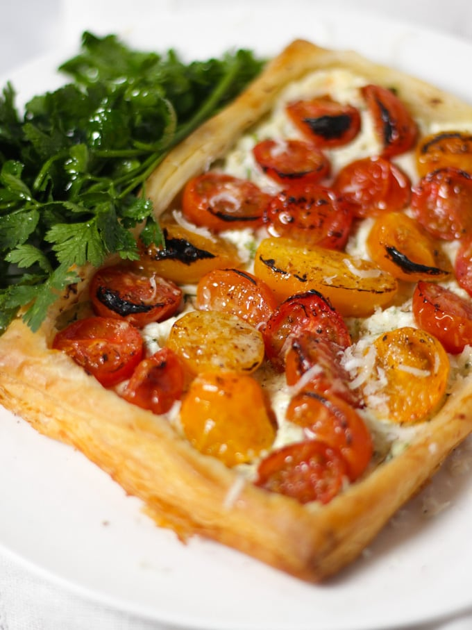 Tomato and cheese puff pastry tart on a white plate with bunch of parsley
