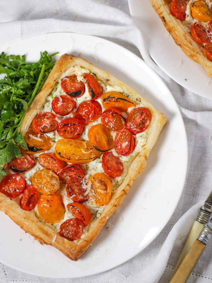 Puff pastry tart with ricotta cheese, tomatoes and parsley on a white plate.