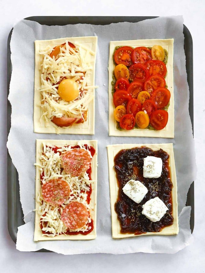 Raw uncooked puff pastry tart with a variety of toppings