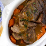 Sliced slow cooked joint of beef with carrots and onions