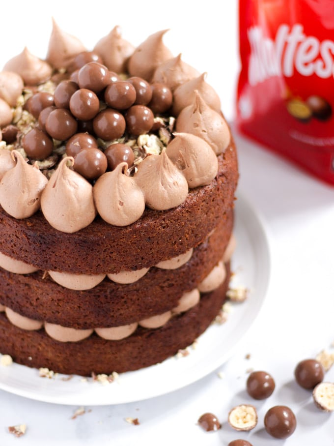 Malteser cake pilled with chocolate frosting and malt balls on a white plate