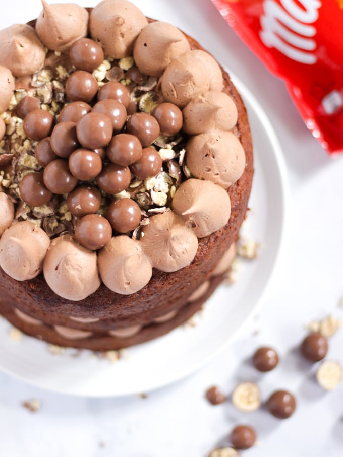 Malteser Cake on a white plated with bag of chocolates in background