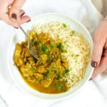 Hands holding a bowl of healthy slow cooker chicken curry with rice