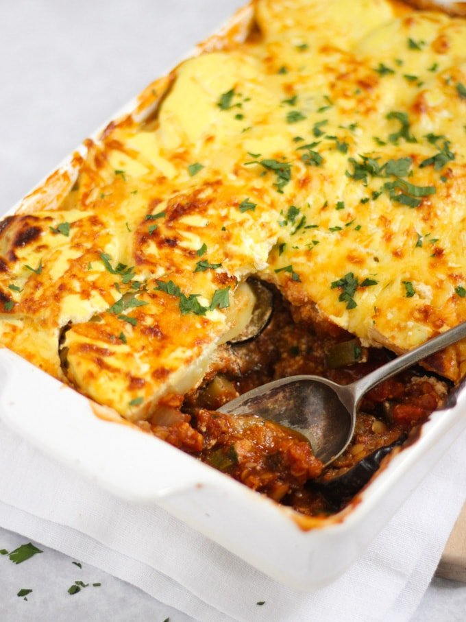 Vegetarian moussaka in a white casserole dish sprinkled with herbs