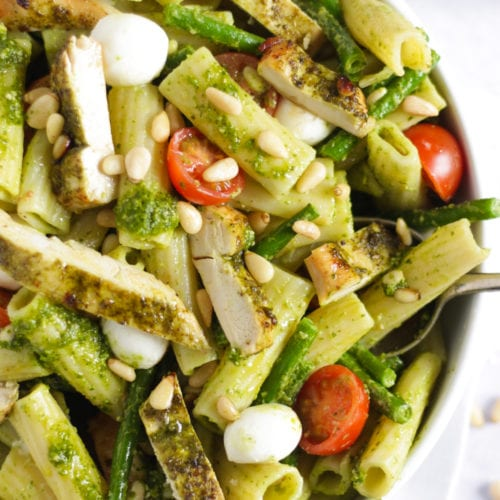 Chicken pesto pasta bake with tomatoes and green beans in a white bowl
