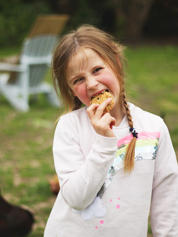 Girl eating an oatmeal cookie with garden in background
