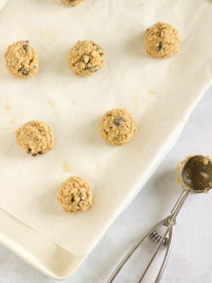 Scoops of cookie dough on a baking sheet with ice cream scoop