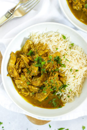 Easy slow cooker chicken curry in bowls with rice sprinkled with mint