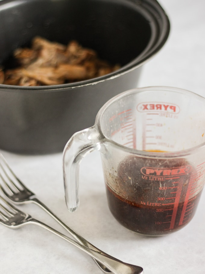 Juices from slow cooker pulled pork in a pyrex jug.