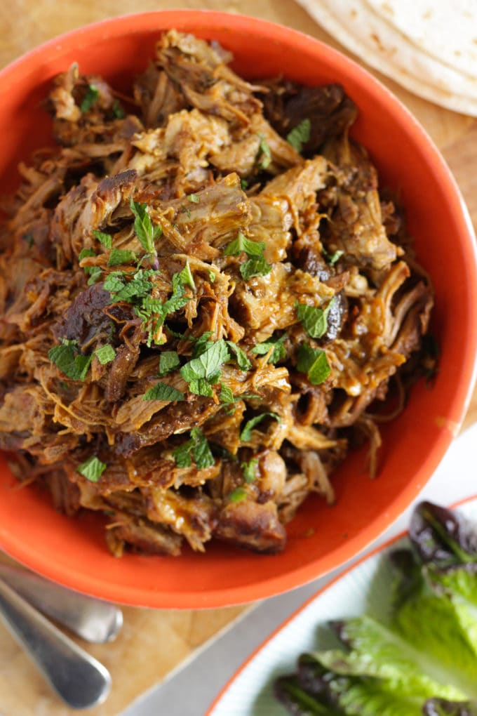 Slow cooker pork shoulder in a red bowl.