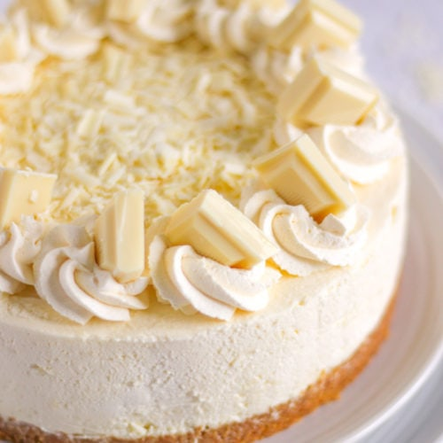 White chocolate cheesecake on a plate with cream and chunks of white chocolate on top