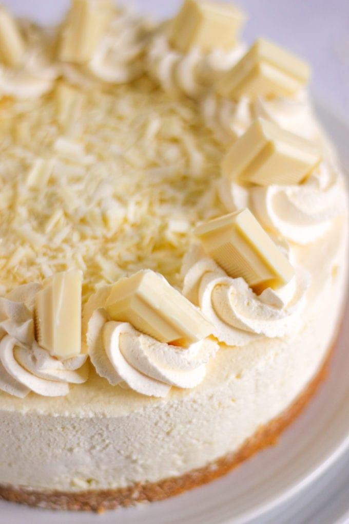 White chocolate cheesecake (no bake) with swirls of cream and chunks of white chocolate on top
